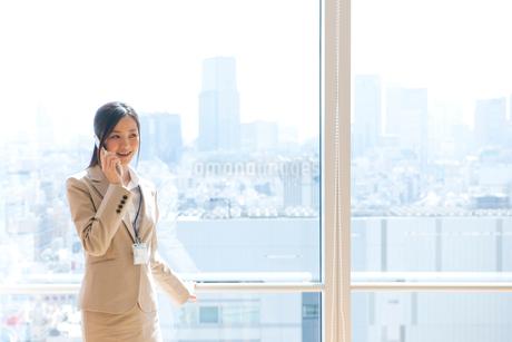 オフィスの窓際で電話をするスーツ姿の女性の写真素材 [FYI02070032]