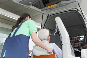介護車両に車いすの男性を乗せる女性介護士の写真素材 [FYI02070037]