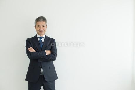 壁を背に立つミドルビジネスマンの写真素材 [FYI02070044]