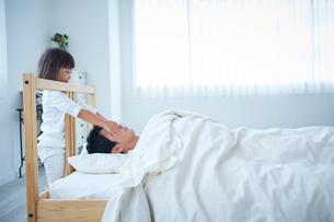 眠っている父親の顔に触れる女の子の写真素材 [FYI02070051]