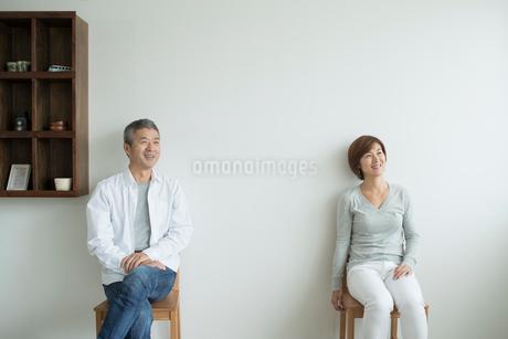 壁を背に椅子に座るミドル夫婦の写真素材 [FYI02070055]