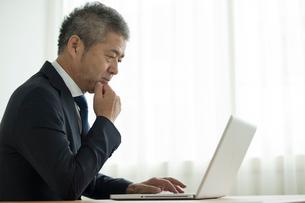 ノートパソコンを見るミドル男性の写真素材 [FYI02070064]