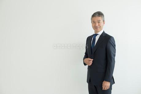 壁を背に立つミドルビジネスマンの写真素材 [FYI02070065]