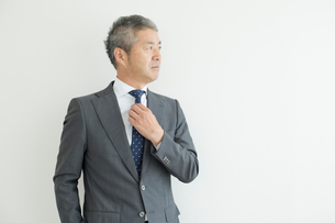 壁を背に立つミドルビジネスマンの写真素材 [FYI02070136]