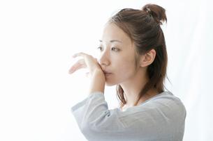 手で口を拭う若い女性の写真素材 [FYI02070138]