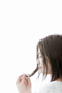 枝毛を気にする若い女性の写真素材 [FYI02070143]