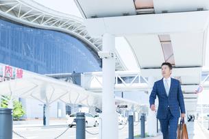 空港の前を歩くミドル世代のビジネスマンの写真素材 [FYI02070148]