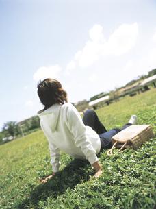 芝生に座る女性後姿の写真素材 [FYI02070170]