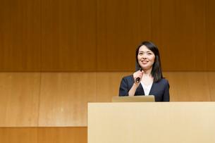 演台でマイクを持って話すスーツ姿の女性の写真素材 [FYI02070174]
