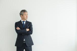 壁を背に立つミドルビジネスマンの写真素材 [FYI02070176]