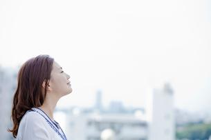 街並を眺める若い女性の写真素材 [FYI02070186]