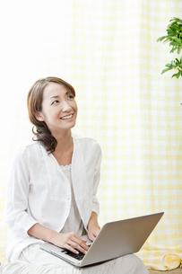 ノートパソコンを膝に乗せた若い女性の写真素材 [FYI02070190]