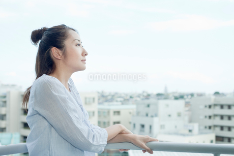 バルコニーから外を眺める若い女性の写真素材 [FYI02070193]