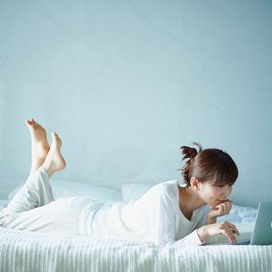 ベッドでノートパソコンを操作する女性の写真素材 [FYI02070209]