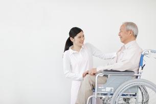 車椅子に乗るシニア男性と女性介護士の写真素材 [FYI02070220]