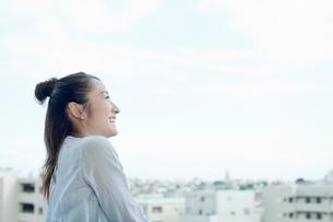 バルコニーで笑顔で空を見上げる若い女性の写真素材 [FYI02070257]