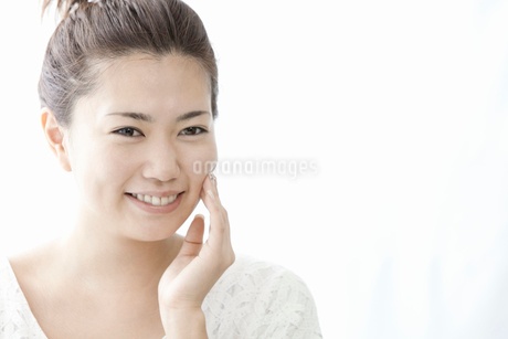 手で頬をさわる若い女性の写真素材 [FYI02070258]