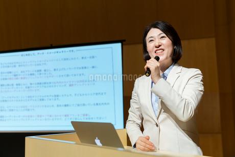 演台で話すスーツ姿のミドル女性とプロジェクタースクリーンの写真素材 [FYI02070280]