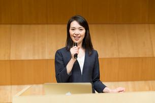 演台でマイクを持って話すスーツ姿の女性の写真素材 [FYI02070281]