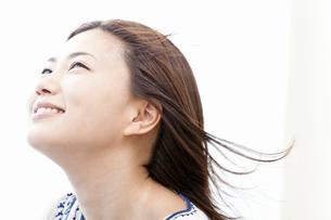 風を受けて微笑む若い女性の写真素材 [FYI02070289]