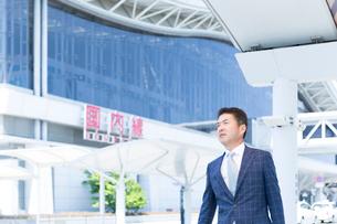 空港の前を歩くミドル世代のビジネスマンの写真素材 [FYI02070316]