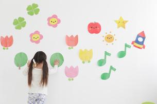 壁に貼ったイラストと女の子の後ろ姿のイラスト素材 [FYI02070325]