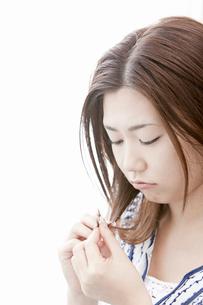 枝毛を気にする若い女性の写真素材 [FYI02070339]