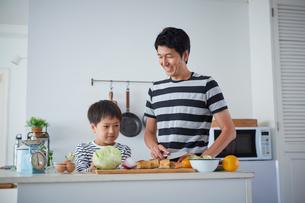 料理をする男の子と父親の写真素材 [FYI02070342]