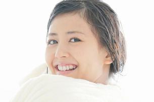 タオルで髪の毛を拭きながら笑顔でこちらを見る若い女性の写真素材 [FYI02070348]
