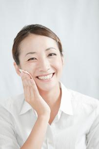 化粧落としで顔を拭く若い女性の写真素材 [FYI02070350]