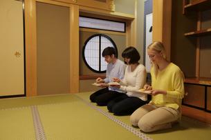 茶菓子を食べる外国人3人の写真素材 [FYI02070428]