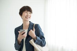 スマートフォンを持つミドル女性の写真素材 [FYI02070431]