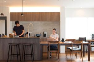 料理をする男性とノートパソコンを操作する女性の写真素材 [FYI02070439]