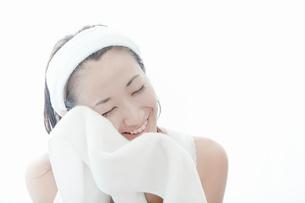 タオルで顔を拭く若い女性の写真素材 [FYI02070446]