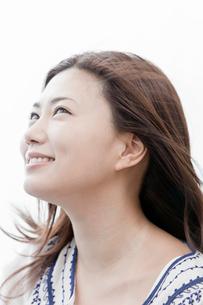 風を受けて微笑む若い女性の写真素材 [FYI02070453]
