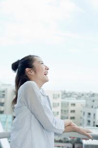 バルコニーで笑顔で空を見上げる若い女性の写真素材 [FYI02070467]