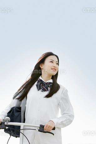 自転車を押しながら歩く女子高校生の写真素材 [FYI02070475]