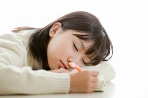 ペンを持ったまま居眠りをする女子高校生の写真素材 [FYI02070485]