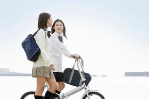笑顔で会話をしながら通学する女子高校生の写真素材 [FYI02070533]