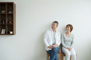 壁を背に椅子に座るミドル夫婦の写真素材 [FYI02070565]
