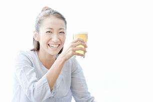 ビールを手に持ち笑顔の若い女性の写真素材 [FYI02070576]