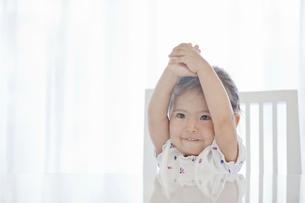 テーブルに腰掛ける女の子の写真素材 [FYI02070629]