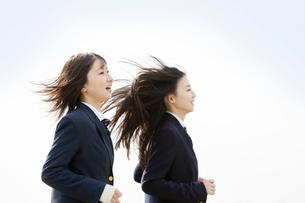 髪をなびかせて走る2人の女子高校生の写真素材 [FYI02070635]