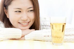 グラスに注がれたビールを見つめる若い女性の写真素材 [FYI02070658]