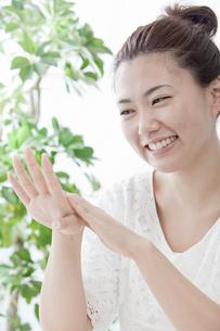 化粧水を手に塗る若い女性の写真素材 [FYI02070669]