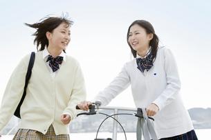 笑顔で会話をしながら通学する女子高校生の写真素材 [FYI02070720]