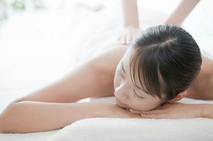 うつ伏せで背中をマッサージされている若い女性の写真素材 [FYI02070750]