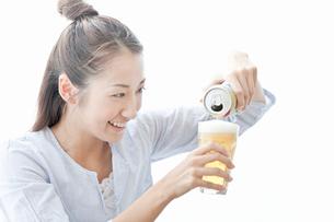 缶ビールをグラスに注ぐ若い女性の写真素材 [FYI02070812]