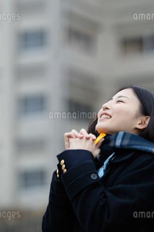 お守りを持ち祈る女子高校生の写真素材 [FYI02070821]