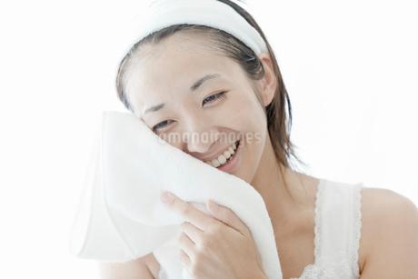 タオルで顔を拭く若い女性の写真素材 [FYI02070859]